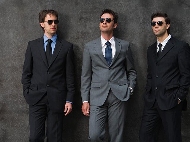 tres hombres portando trajes color negro
